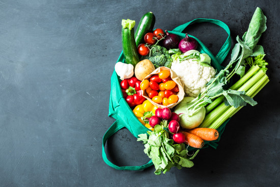 Colorful organic vegetables in green eco shopping bag - captured from above