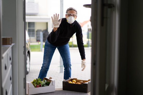 Man in face mask and gloves delivering boxes of food